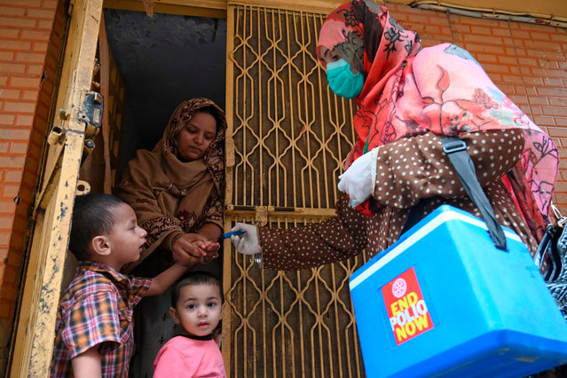 A health worker (R) marks the finger of a child after administering polio vaccine drops during a polio vaccination door-to-door campaign in Lahore on July 20, 2020. Pakistan on July 20 resumed its polio vaccination campaign after a four-month pause due to the coronavirus outbreak, with health authorities predicting a surge in cases of the crippling disease. (Photo by Arif Ali/AFP Photo)