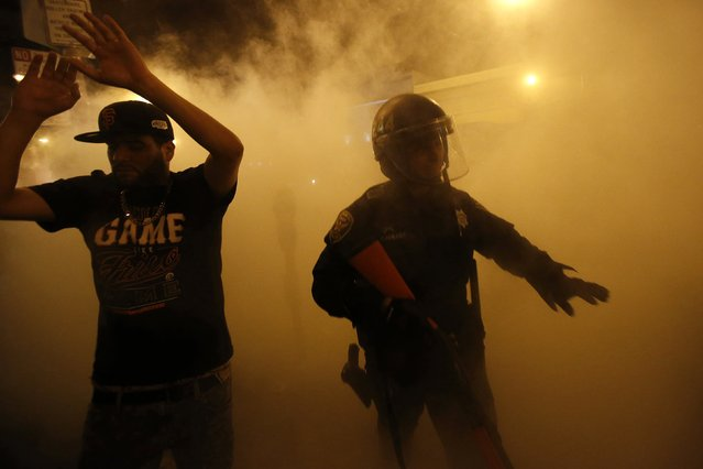 A reveller raises his arms after being ordered to disperse by the police during a street celebration in San Francisco, California October 29, 2014. (Photo by Stephen Lam/Reuters)