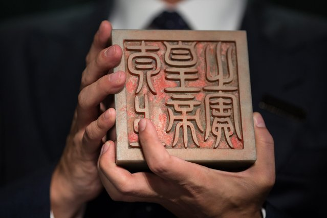 Nicolas Chow, deputy chairman of Sotheby's Asia, international head and chairman of Chinese works of art, holds the Imperial Khotan Jade Taishang Huangdi zhi Bao Seal from the Qing Dynasty, Qianlong Period during an auction preview in Hong Kong, China, 08 September 2016. The seal is estimated to fetch between 10 to 15 million US dollar. Sotheby's Chinese Works of Art Autumn Sales 2016 will take place on 05 October in Hong Kong, offering close to 300 lots with a total estimate of approximately 80 million US dollar. (Photo by Jerome Favre/EPA)