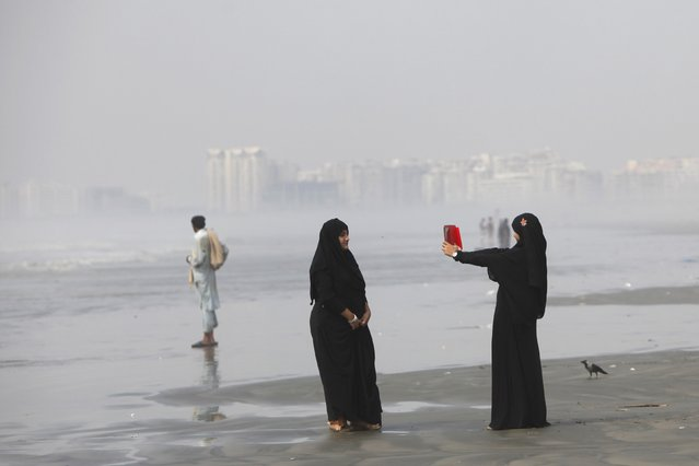 Girls clad in burqas take picture with a tablet while visiting Karachi's Clifton beach October 28, 2014. According to local media, Pakistan authorities closed coastal belt due to the tropical cyclone Nilofar which has gained further strength as it continue to move inwards. (Photo by Akhtar Soomro/Reuters)