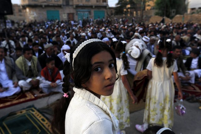 A Yemeni girl looks back, away from the festival crowd, as she attends the Eid al-Adha prayers at a square in Sana'a, Yemen, 12 September 2016. Eid al-Adha is the holiest of the two Muslims holidays celebrated each year, it marks the yearly Muslim pilgrimage (Hajj) to visit Mecca, the holiest place in Islam. Muslims slaughter a sacrificial animal and split the meat into three parts, one for the family, one for friends and relatives, and one for the poor and needy. (Photo by Yahya Arhab/EPA)