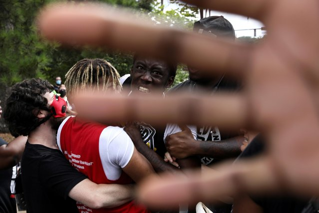 A counter-protester is held back after being sprayed with pepper spray as various militia groups stage rallies in downtown Stone Mountain, Georgia, U.S. August 15, 2020. (Photo by Dustin Chambers/Reuters)