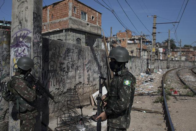 Soldiers patrol next to the railway lines during a surprise operation in the Jacarezinho slum in Rio de Janeiro, Brazil, Thursday, January 18, 2018. (Photo by Leo Correa/AP Photo)