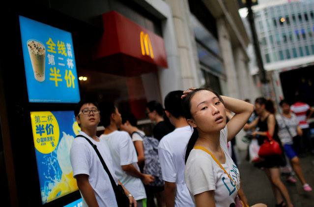 Customers stand outside of a McDonald's store in downtown Shanghai July 31, 2014. (Photo by Carlos Barria/Reuters)