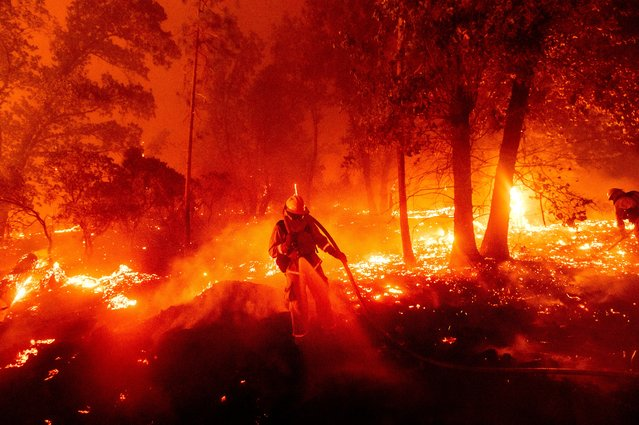 A firefighter battles the Creek Fire as it threatens homes in the Cascadel Woods neighborhood of Madera County, Calif., on Monday, September 7, 2020. (Photo by Noah Berger/AP Photo)