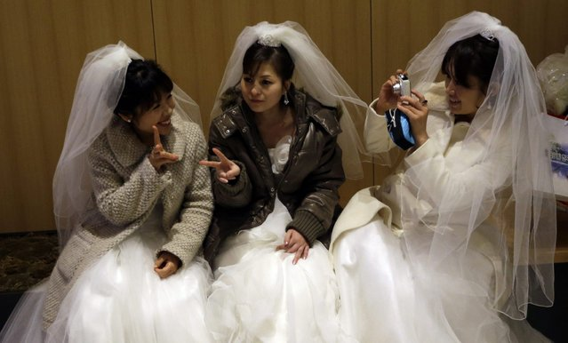 Brides take their souvenir pictures each others before their mass wedding ceremony at the CheongShim Peace World Center in Gapyeong, South Korea, Sunday, February 17, 2013. Some 3,500 South Korean and foreign couples exchanged or reaffirmed marriage vows in the Unification Church's mass wedding arranged by Hak Ja Han Moon, a wife of the late Rev. Sun Myung Moon, the controversial founder of the Unification Church. (Photo by Lee Jin-man/AP Photo)