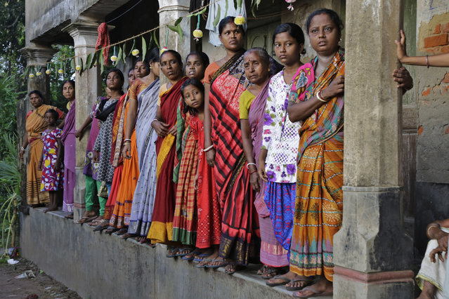 Villagers wait on a verandah to witness the funeral procession of Indian army soldier Gangadhar Dalai, who was killed in a militant attack in Uri, Kashmir, in Jamuna Balia village, west of Kolkata, India, Tuesday, September 20, 2016. Early Sunday, fighters slipped into an army base in Indian-controlled Kashmir, killing at least 15 soldiers. (Photo by Bikas Das/AP Photo)