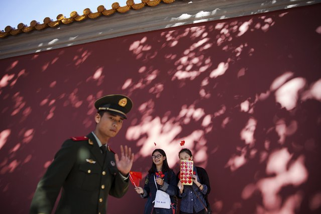 A paramilitary policeman walks past girls offering flags, stickers and hairpins in national colours to people gathering near the Tiananmen Gate on National Day marking the 66th anniversary of the founding of the People's Republic of China, in Beijing October 1, 2015. (Photo by Damir Sagolj/Reuters)