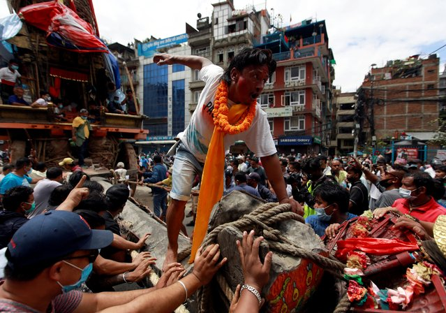 A man reacts as people pull the chariot of Rato Machhindranath amid the ban on public and religious gatherings to control the spread of coronavirus disease (COVID-19) in Lalitpur, Nepal on September 3, 2020. (Photo by Navesh Chitrakar/Reuters)