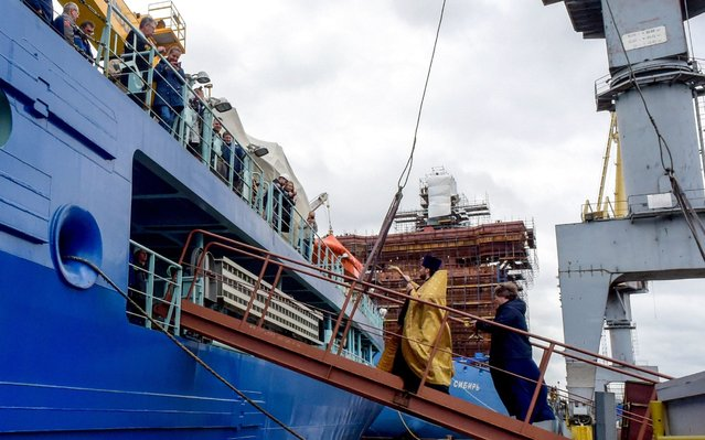 Russian Orthodox priest blesses the Russia's nuclear-powered icebreaker Arktika at the port in Saint Petersburg on September 22, 2020. Russia's nuclear-powered icebreaker Arktika, touted as the most powerful of its kind and a symbol of Moscow's Arctic ambitions, set off on its maiden voyage on September 22, 2020. Designed to transport liquefied natural gas from the Arctic, the giant vessel is 173 metres (570 feet) long and 15 metres high. (Photo by Olga Maltseva/AFP Photo)