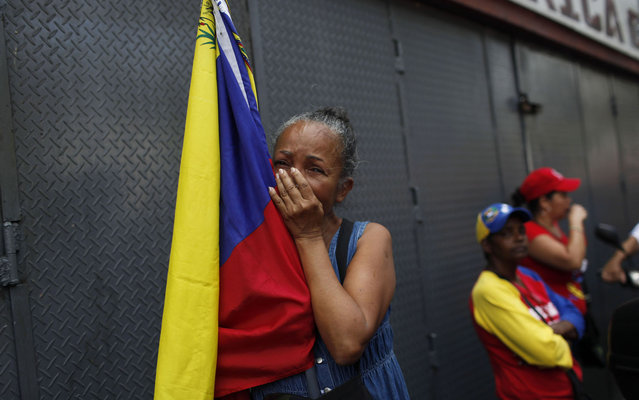 A woman holding a Venezuelan flag cries as she watches the coffin containing the body of the late President Hugo Chavez be taken from the hospital, where he died on Tuesday, to a military academy in Caracas, Venezuela, Wednesday, March 6, 2013. Seven days of mourning were declared, all schools were suspended for the week and friendly heads of state were expected for an elaborate funeral on Friday. (Photo by Rodrigo Abd/AP Photo)