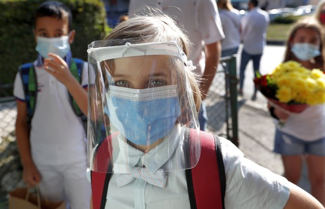 """A student wearing a face shield waits to enter during his first day of school at """"George Enescu"""" National College of Music in Bucharest, Romania, 14 September 2020. Children get accustomed with health safety measures and receive textbooks and timetables for the first semester. (Photo by Robert Ghement/EPA/EFE)"""