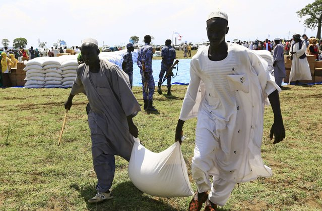 Men carry a sack after receiving food provided by the United Nations' World Food Programme (WFP) during a visit by a European Union delegation, at an Internally Displaced Persons (IDP) camp in Azaza, east of Ad Damazin, capital of Blue Nile state, Sudan October 21, 2015. (Photo by Mohamed Nureldin Abdallah/Reuters)