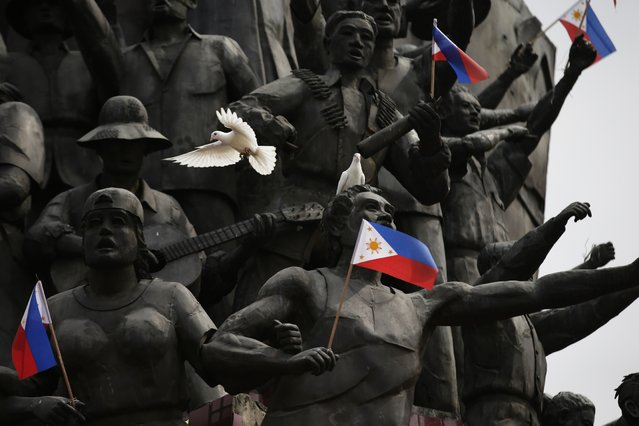 """Pigeons gather at the People Power monument during the celebration Tuesday, February 25, 2014 at suburban Quezon city northeast of Manila, Philippines, of the 28th anniversary of the near-bloodless revolt known as People Power that toppled the late dictator Ferdinand Marcos from 20-year-rule and helped install Corazon """"Cory"""" Aquino, the mother of President Benigno Aquino III, to the Presidency. President Aquino III led for the first time Tuesday the celebration in Cebu in central Philippines. (Photo by Bullit Marquez/AP Photo)"""
