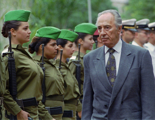 Israeli Prime Minister Shimon Peres, also serving as the country's Defense Minister, is greeted by a military honor guard as he arrives at the Defense Ministry in Tel Aviv Thursday November 23 1995. Peres was sworn in as Israel's Prime Minister and Defense Minister Wednesday, taking over from assassinated Premier Yitzhak Rabin. (Photo by Nati Harnik/AP Photo)