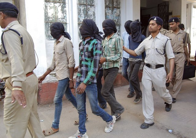 Police escort men accused of a gang rape to a court in Datia district in the central Indian state of Madhya Pradesh March 18, 2013. Police have arrested six men accused of the gang-rape of a Swiss tourist who was camping with her husband in an Indian forest in the central state of Madhya Pradesh. (Photo by Reuters/Stringer)