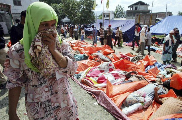 An Acehnese woman covers her nose as she walks past thousands of dead bodies in the Indonesian city of Banda Aceh in this December 27, 2004 file photo. (Photo by Reuters/Beawiharta)
