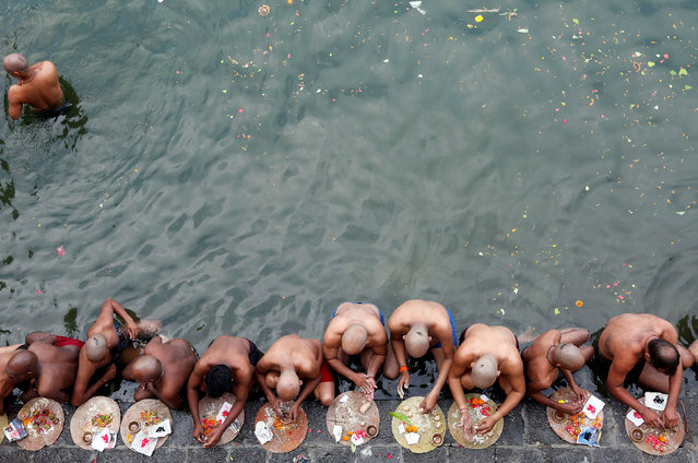 Hindu devotees pray in the waters of the river Ganga as they take a dip to honour the souls of their departed ancestors on the auspicious day of Mahalaya, which is also called Shraadh or Pitru Paksha, in Allahabad, India, September 30, 2016. (Photo by Shailesh Andrade/Reuters)