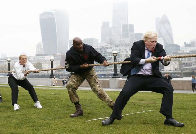 London Mayor Boris Johnson takes part in a tug of war with members of the armed services to launch the London Poppy Day, outside City Hall, in London, October 27, 2015. London Poppy Day is a street collection event to raise money for serving and retired members of the armed services and their families. (Photo by Stefan Wermuth/Reuters)