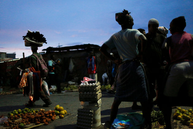 Vendors wait for clients at a street market while Hurricane Matthew approaches in Port-au-Prince, Haiti, October 2, 2016. (Photo by Carlos Garcia Rawlins/Reuters)