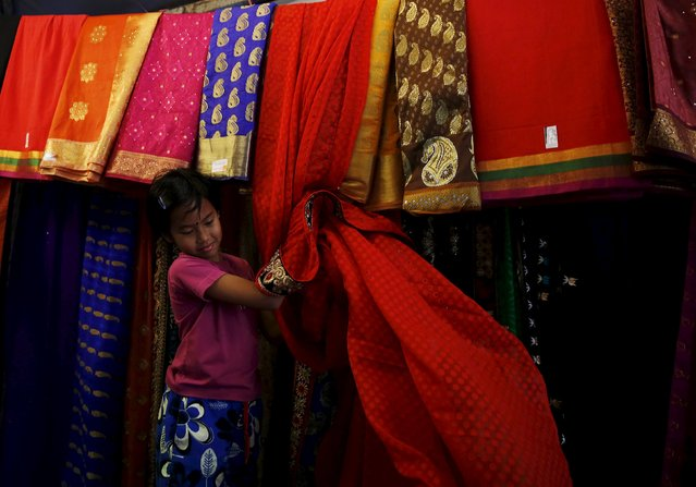A girl works on a market stall selling saris for Diwali celebrations in Kuala Lumpur, Malaysia, October 28, 2015. (Photo by Olivia Harris/Reuters)