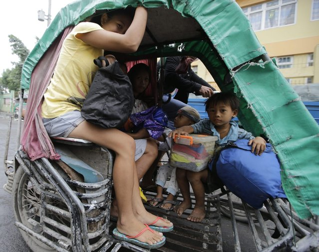 Residents living along coastal areas in Manila evacuate to safer grounds as the local government ordered the pre-emptive evacuation in anticipation of Typhoon Hagupit which is expected to make its fourth landfall Monday, December 8, 2014 in Manila, Philippines. Typhoon Hagupit weakened into a storm Monday after it left at least three people dead and sent more than a million others into shelters, sparing the central Philippines the massive devastation that a monster storm inflicted on the region last year. (Photo by Bullit Marquez/AP Photo)
