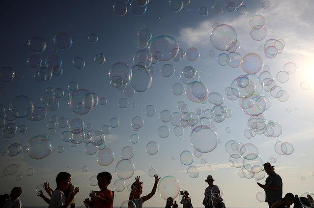 Children try to burst soap bubbles during hot weather at Brighton beach in Brighton, Britain on September 15, 2020. (Photo by Hannah McKay/Reuters)