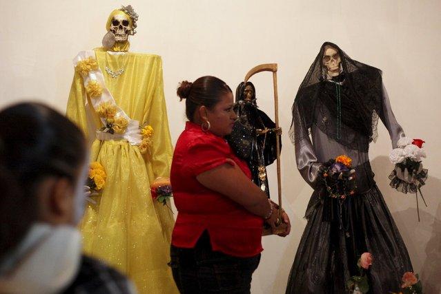 A woman carries a figurine of La Santa Muerte (Saint Death) at a shrine during Day of the Dead celebrations in Ciudad Juarez, Mexico, November 2, 2015. (Photo by Jose Luis Gonzalez/Reuters)