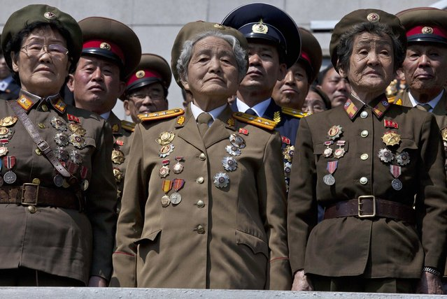 Retired North Korean military members stand at attention during an induction ceremony for children into the Korean Children's Union, the first political organization for North Koreans, held at a stadium in Pyongyang on Friday, April 12, 2013. (Photo by David Guttenfelder/AP Photo)