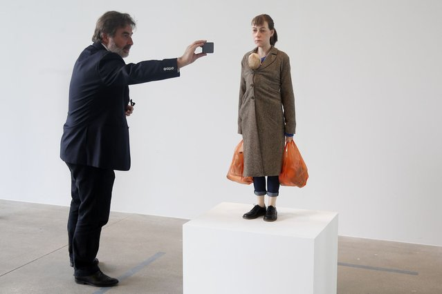 "A visitor takes a picture of a sculpture entitled ""Woman with Shopping, 2013"" by artist Ron Mueck during the press day for his exhibition at the Fondation Cartier pour l'art contemporain in Paris April 15, 2013. (Photo by Charles Platiau/Reuters)"