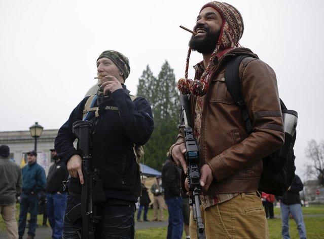Douglas MacPhail Reynolds (L) and Chris Williams smoke cigars as gun rights advocates rally against Initiative 594 at the state capitol in Olympia, Washington December 13, 2014. (Photo by Jason Redmond/Reuters)