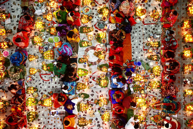 Hindu devotees sit together on the floor of a temple with oil lamps to pray to the Lokenath Brahmachari, a Hindu saint, as they observe Rakher Upabash, in Dhaka, Bangladesh, November 14, 2020. (Photo by Mohammad Ponir Hossain/Reuters)