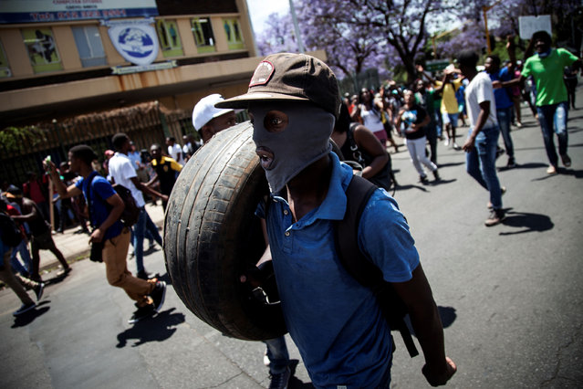 A protester from the  Tshwane University of Technology (TUT), carries a tyre during a march through Pretoria to close down all campuses, on October 12, 2016. Weeks of protests at South African universities have targeted tuition fees – but students say they are also about racism and inequality in a society still plagued by the legacy of apartheid. The demonstrations have tapped into deep problems in the country, where many black people are unable to get decent education, jobs or housing despite white minority rule ending more than 20 years ago. (Photo by John Wessels/AFP Photo)