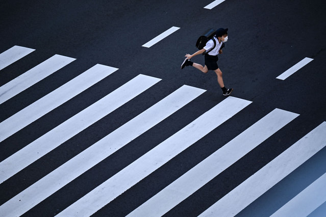 A school student crosses a street in Tokyo on November 10, 2020. (Photo by Charly Triballeau/AFP Photo)