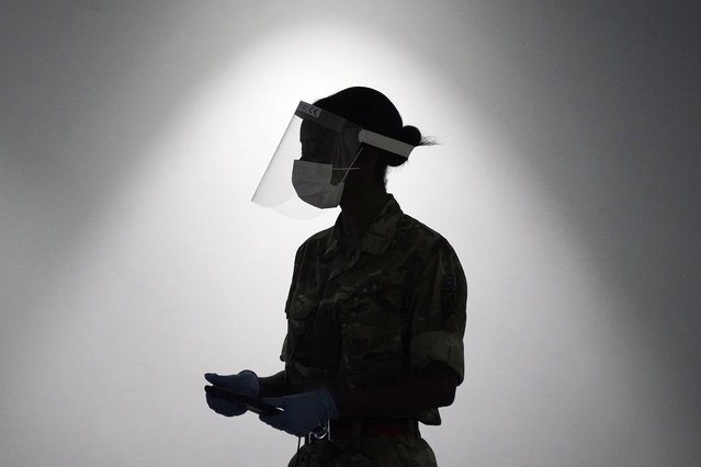 A soldier from the Yorkshire Regiment operates a coronavirus disease (Covid-19) testing centre at Liverpool Exhibition Centre on November 11, 2020 in Liverpool, England. More than 23,000 people had been tested for covid-19 in the first three days of the city's mass testing trial. In that time, 154 people tested positive. All residents and workers in the city were offered the test. (Photo by Christopher Furlong/Getty Images)
