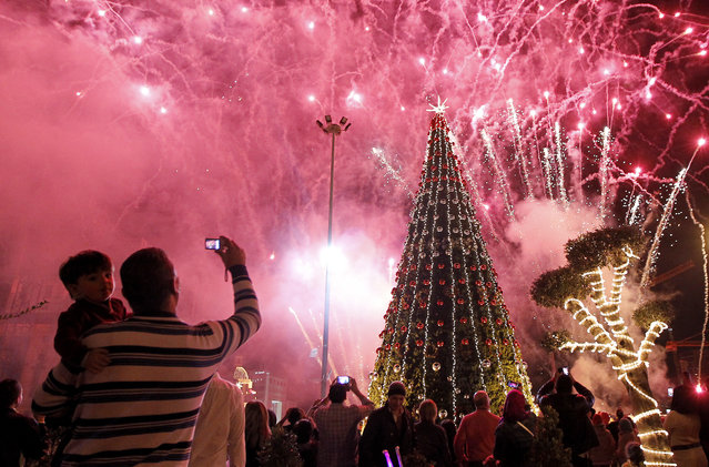 """Fireworks explode over a giant Christmas tree during the event """"Beirut Christmas carnival"""" organized by Beirut municipality in Beirut, Lebanon, December 20, 2014. Beirut is one of the most religiously diverse cities of the Middle East with big Christians and Muslim communities.  (Photo by Nabil Mounzer/EPA)"""