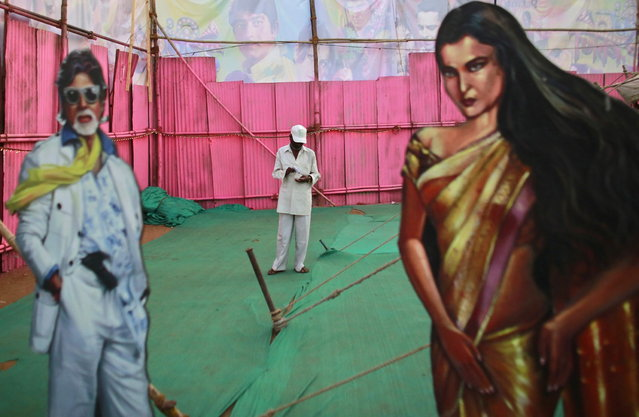 An employee of Anoop Touring Talkies, a travelling tent cinema company, stands between cut-outs of Bollywood actors Amitabh Bachchan and Rekha in Mumbai April 23, 2013. (Photo by Danish Siddiqui/Reuters)