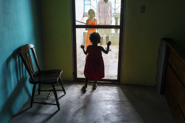 Berlinda, stands at the screen door while others talk outside on Sunday September 21, 2014 in Monrovia, Liberia. Berlina mother died of Ebola in an ambulance on the way to Redemption Hospital. The child is Berlinda is under observation for signs of Ebola and was isolated for 21 days. She was rescued by Katie Meyler and is being cared for by the NGO called More than Me (run by Meyler). (Photo by Michel du Cille/The Washington Post)