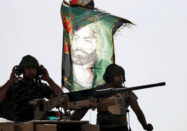 Iraqi special forces soldiers sit on top of an armoured vehicle next to a flag of Imam Hussein in Bartella, east of Mosul, Iraq October 20, 2016. (Photo by Goran Tomasevic/Reuters)