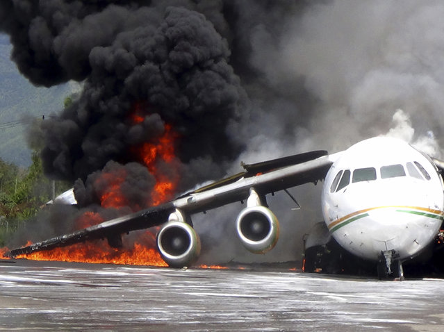 Smoke billows from a British-made BAe 146 cargo plane that caught fire while being unloaded at the airport in Wamena, Papua province, Indonesia, Wednesday, May 8, 2013. An official said that the plane caught fire after a drum of oil fell from the aircraft and somehow sparked the fire. (Photo by AP Photo)