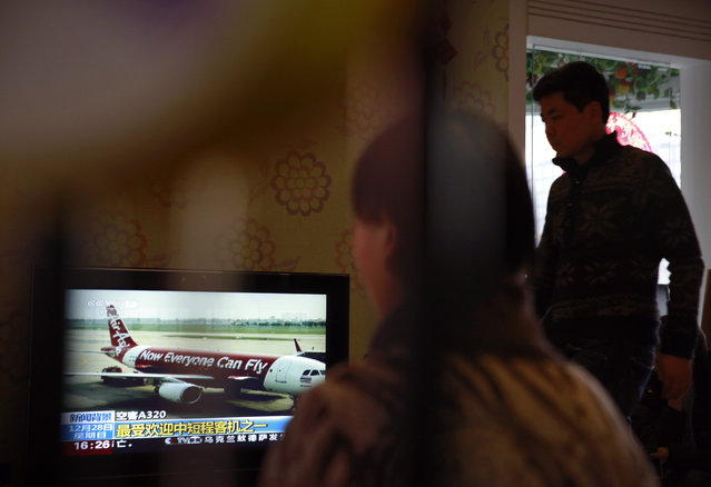 Relatives of passengers onboard the Malaysia Airlines Flight 370 that went missing on March 8, 2014, watch TV news about missing AirAsia flight QZ8501, during their year-end gathering at a house in Beijing, China Sunday, December 28, 2014. In the third air incident connected to Malaysia this year, an AirAsia plane disappeared on Sunday while flying over the Java Sea after taking off from Surabaya, Indonesia for Singapore. (Photo by Andy Wong/AP Photo)
