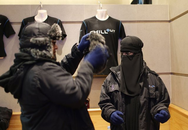 Ahmed, a Saudi Arabian, helps his newly-wed wife Nofa put on a fur hat at Chillout cafe in Dubai May 12, 2013. (Photo by Ahmed Jadallah/Reuters)