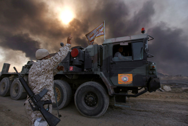 Iraqi army are seen in Qayyara, Iraq, October 22, 2016. The fumes in the background are from oil wells that were set ablaze by Islamic State militants. (Photo by Alaa Al-Marjani/Reuters)
