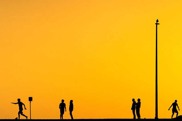 Silhouettes of people enjoying the sunset at Huntington Beach, California on November 25, 2020. Huntington Beach is also known as Surf City USA and is a travel destination in Southern California. (Photo by Ronen Tivony/SOPA Images/Rex Features/Shutterstock)