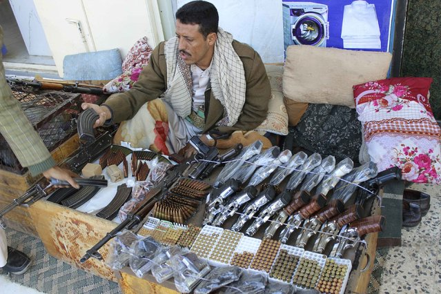 A man holds a rifle magazine as he sits at his stall on a street in the northwestern city of Saada December 27, 2014. (Photo by Naiyf Rahma/Reuters)