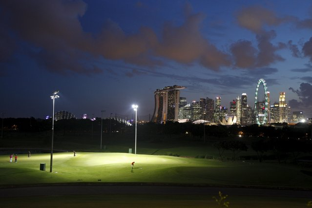 Golfers practise at the public Marina Bay Golf Course built on reclaimed land, Singapore July 21, 2015. (Photo by Edgar Su/Reuters)