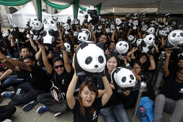 """Volunteers pose for photographers with the part of the 1,600 paper pandas, created by French artist Paulo Grangeon, before the paper pandas to be displayed in front of the Sultan Abdul Samad Building during the month-long """"1600 Pandas World Tour"""" in Kuala Lumpur, Malaysia, Sunday, December 21, 2014. (Photo by Lai Seng Sin/AP Photo)"""