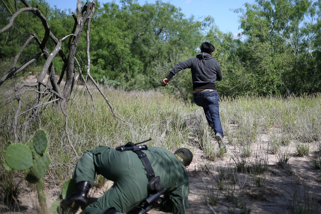 A man who illegally crossed the Mexico-U.S. border evades a U.S. Border Patrol agent near McAllen, Texas, U.S., May 8, 2018. (Photo by Loren Elliott/Reuters)