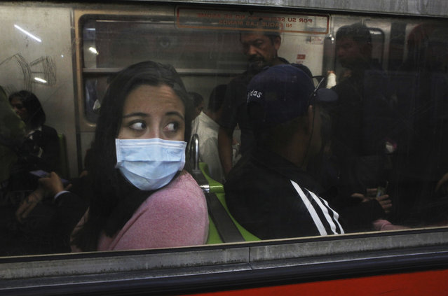 A commuter in the metro wears a protective mask as a precaution against the spread of the new coronavirus in Mexico City, Thursday, March 19, 2020. (Photo by Marco Ugarte/AP Photo)