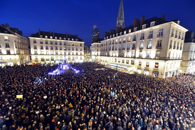 People gather at the Place Royale in Nantes on January 7, 2015, to show their solidarity for the victims of the attack by unknown gunmen on the offices of the satirical weekly, Charlie Hebdo. Heavily armed gunmen massacred 12 people on Wednesday after bursting into the Paris offices of a satirical weekly that had long outraged Muslims with controversial cartoons of the prophet Mohammed. (Photo by Georges Gobet/AFP Photo)